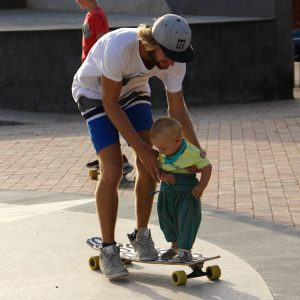 Carl teaches a baby how to ride a Longboard