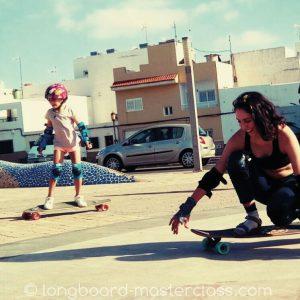 Mutter und Kind beim Longboard fahren lernen im Anfängerkurs.